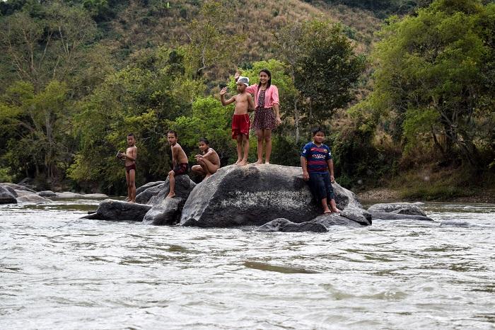 Bambini nel Maekok salutano le barche con a bordo gli stranieri